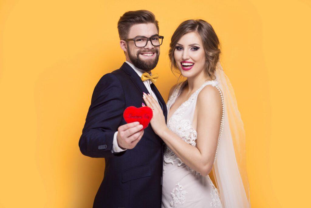 Junges Paar for einer Fotobox mit einem roten Herzen
