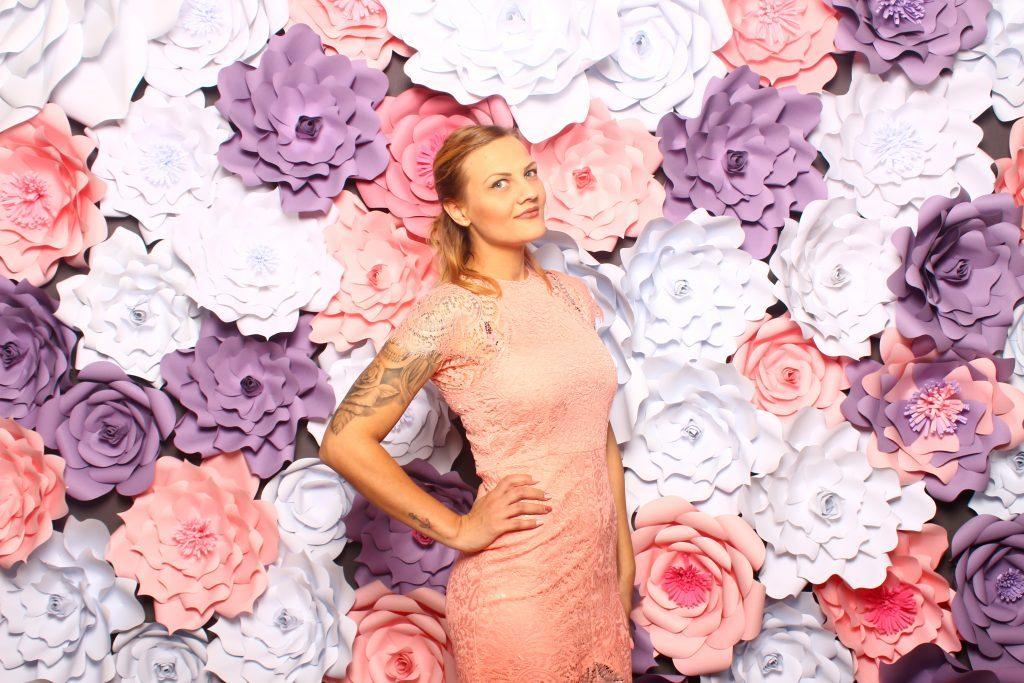 Junge Frau posiert vor Fotobox Blumenhintergund
